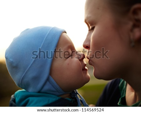 Little boy kissing his mom. Natural light, real colors, shallow DOF (prime 35mm L lense).