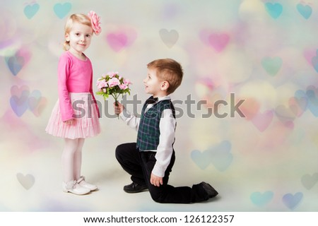 Little boy kneels on one knee giving flowers to girl. Hearts bokeh background. st valentine's day present. Romantic gift
