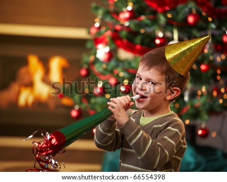Little boy laughing on new year's eve, wearing shiny hat and blowing horn, looking at camera, christmas tree in background.?