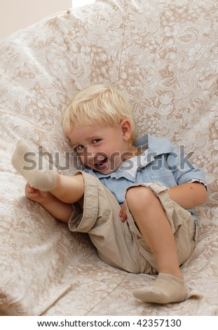 Little boy laught and sit in a room