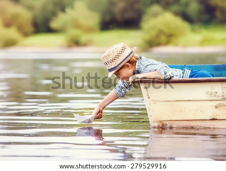 Little boy launch paper ship from old boat on the lake