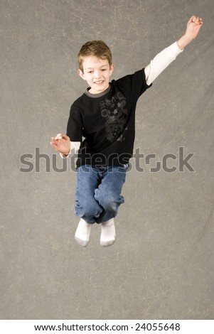 little boy leaping into air over gray background