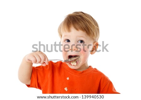 Little boy learning to feed herself - eating the oatmeal with a spoon, isolated on white