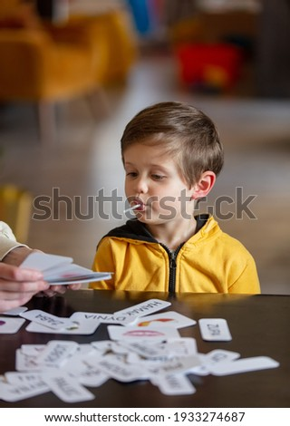 little boy learns words from cards under the ABA therapy program at home at the table  Stock photo ©