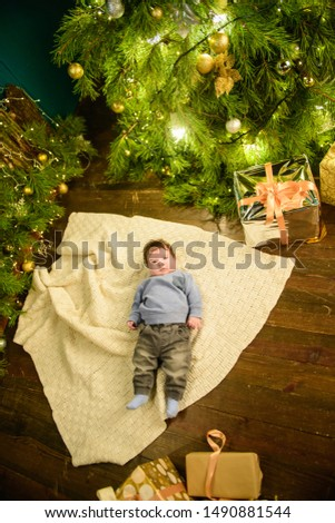 little boy lies near the Christmas tree. Happy little boy is lies near fir-tree. New Year's holidays. in a striped T-shirt with Santa Claus. Happy little boy is lies near fir-tree on a green blanket. #1490881544