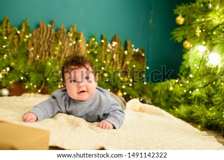 little boy lies near the Christmas tree. Happy little boy is lies near fir-tree. New Year's holidays. in a striped T-shirt with Santa Claus. Happy little boy is lies near fir-tree on a green blanket. #1491142322