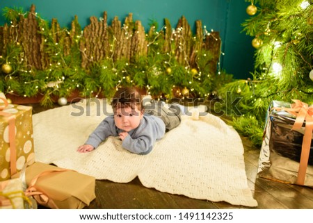 little boy lies near the Christmas tree. Happy little boy is lies near fir-tree. New Year's holidays. in a striped T-shirt with Santa Claus. Happy little boy is lies near fir-tree on a green blanket. #1491142325