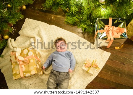 little boy lies near the Christmas tree. Happy little boy is lies near fir-tree. New Year's holidays. in a striped T-shirt with Santa Claus. Happy little boy is lies near fir-tree on a green blanket. #1491142337