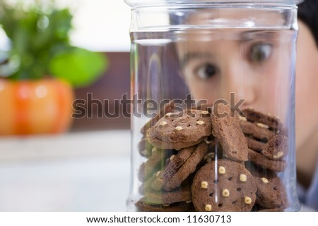 little boy looking at cookies in a jar