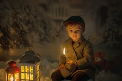 Little boy, looking at flame from match, sitting in the snow, outdoors