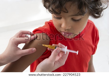 little boy looking at his arm, while receiving vaccine