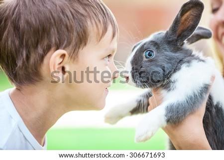 Little boy looking at pet rabbit in mom\'s hands