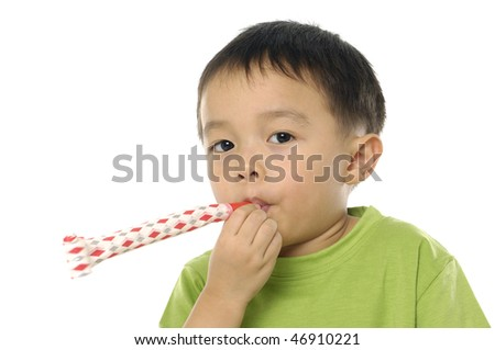 little boy looking at viewer blowing noisemaker