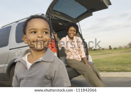 Little boy looking away with woman sitting in the boot of a car