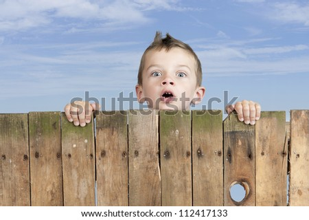 little boy looking from above a fence. Clouds in the background