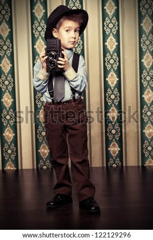 Little boy looking like a gentleman standing with a camera. Vintage background. - stock photo