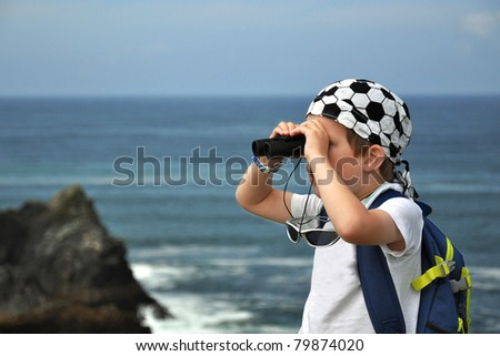 Little boy looking through binoculars, exploring the rocky seascape, with sea and cliff in the background.