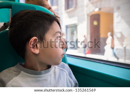little boy looking through the school bus window