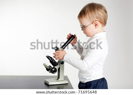 little boy looking to microscope