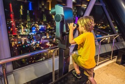 Little boy looks at Kuala lumpur cityscape. Panoramic view of Kuala Lumpur city skyline evening at sunset skyscrapers building in Malaysia. Traveling with kids concept