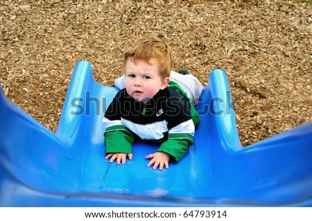Little boy looks up from the bottom of the slide to face a new challenge/Facing a Challenge/Attempt to face the challenges that await