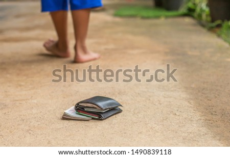 Little boy  lose leather purse with money on the street,Losing wallet concept.