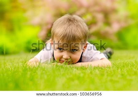 Little boy lying on a green grass