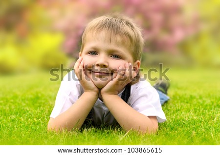 Little boy lying on a green grass
