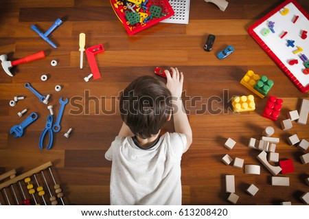 Little boy lying on the wooden floor and playing with colorful toys. Top view ストックフォト ©