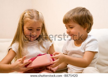 Little boy make a present to his sister