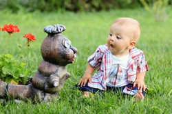 Little boy, making funny faces on a statue in a garden