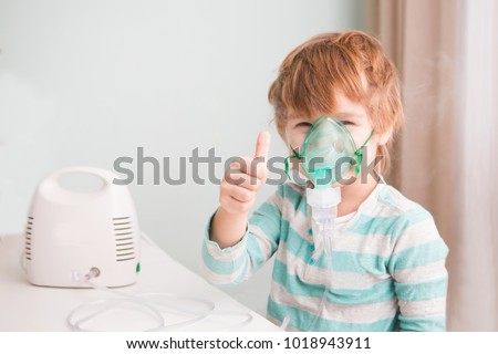 Little boy making inhalation with nebulizer at home.   Foto stock ©
