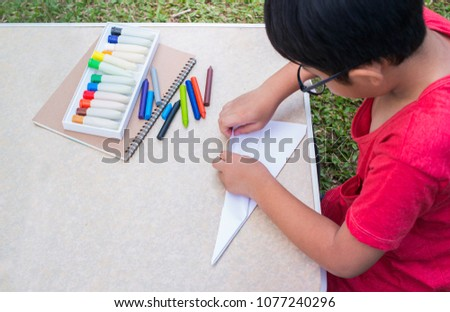 Photo of Little boy making paper plane on table., Top view