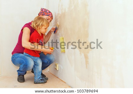 Little boy making renovation with mother, painting the wall