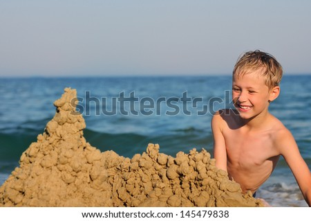 Little boy making sand castle at beach