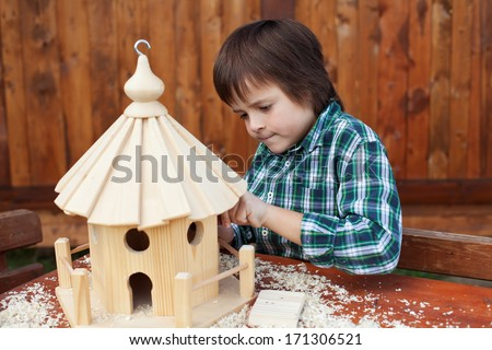 Little boy making the last finishing touches on a wooden bird house he is building