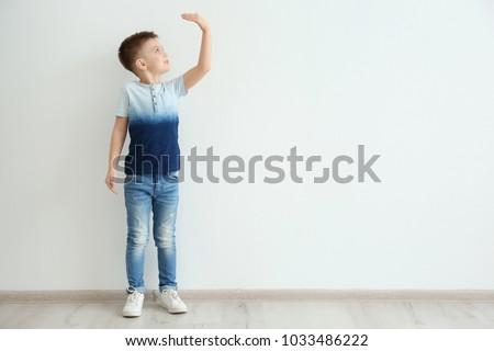 Little boy measuring height near light wall #1033486222