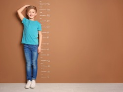 Little boy measuring his height near color wall