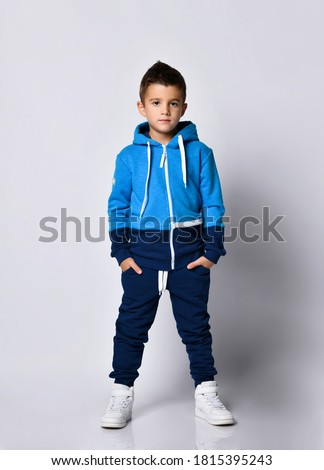 Little boy model wearing sports tracksuit with sweatshirt and pants studio portrait isolated on gray background. Male child posing for camera with hands in pocket. Autumn winter sport children fashion Stock photo ©