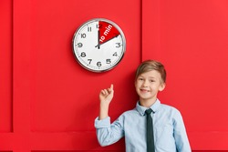 Little boy near clock with timer for 10 minutes on color background. Time management concept