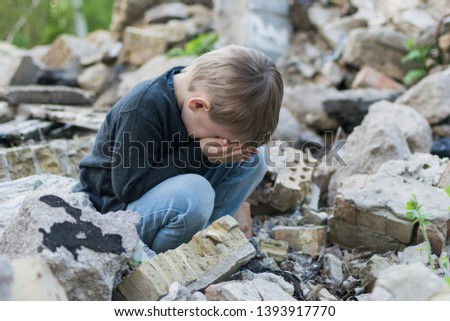 Little boy near the destroyed house. Child trouble, loneliness concept. #1393917770