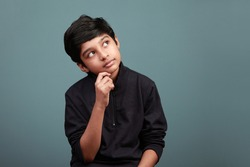 Little boy of Indian ethnicity looking up and thinking