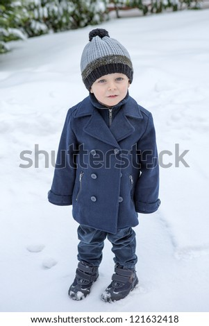 Little boy of two years in winter clothes on day with lot of snow