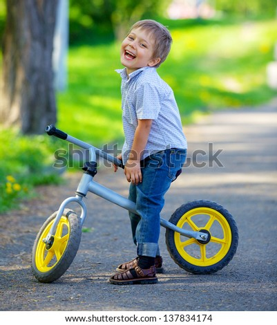 Little boy on a bicycle and his mother in the summer park