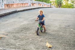 Little boy on a bicycle. Caught in motion, on a driveway motion blurred. Preschool child's first day on the bike. The joy of movement. Little athlete learns to keep balance while riding a bicycle