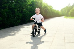Little boy on a bicycle. Caught in motion, on a driveway. Preschool child's first day on the bike. The joy of movement. Little athlete learns to keep balance while riding a bicycle.