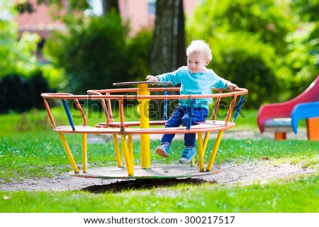Little boy on a playground. Child playing outdoors in summer. Kids play on school yard. Happy kid in kindergarten or preschool. Children having fun at daycare play ground. Toddler on a swing.
