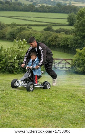 Little boy on a racing a mini moto quad bike with his father riding on the back. Set in countryside.