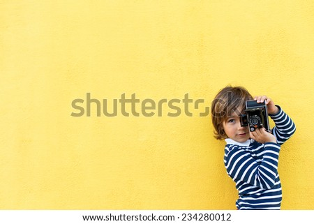 little boy on a yellow wall wearing a stripes sweater taking a photo using a vintage camera