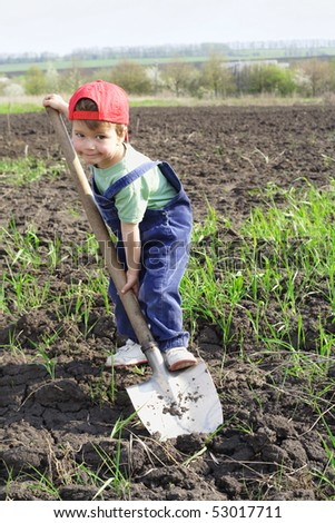 Little boy on field with big shovel, looking to camera